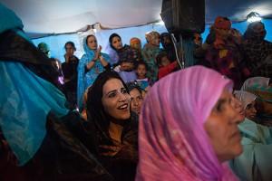 Mujer saharaui se divierte mirando a los bailarines en una fiesta de matrimonio que se lleva a cabo en el campamento. Campamento de refugiados Smara, cerca de Tindouf, Algeria.  2013